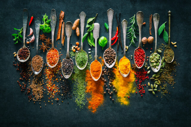 Colorful herbs and spices for cooking on dark background